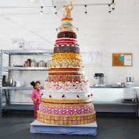 Giant cake with many layers and an astonished child looking up at it
