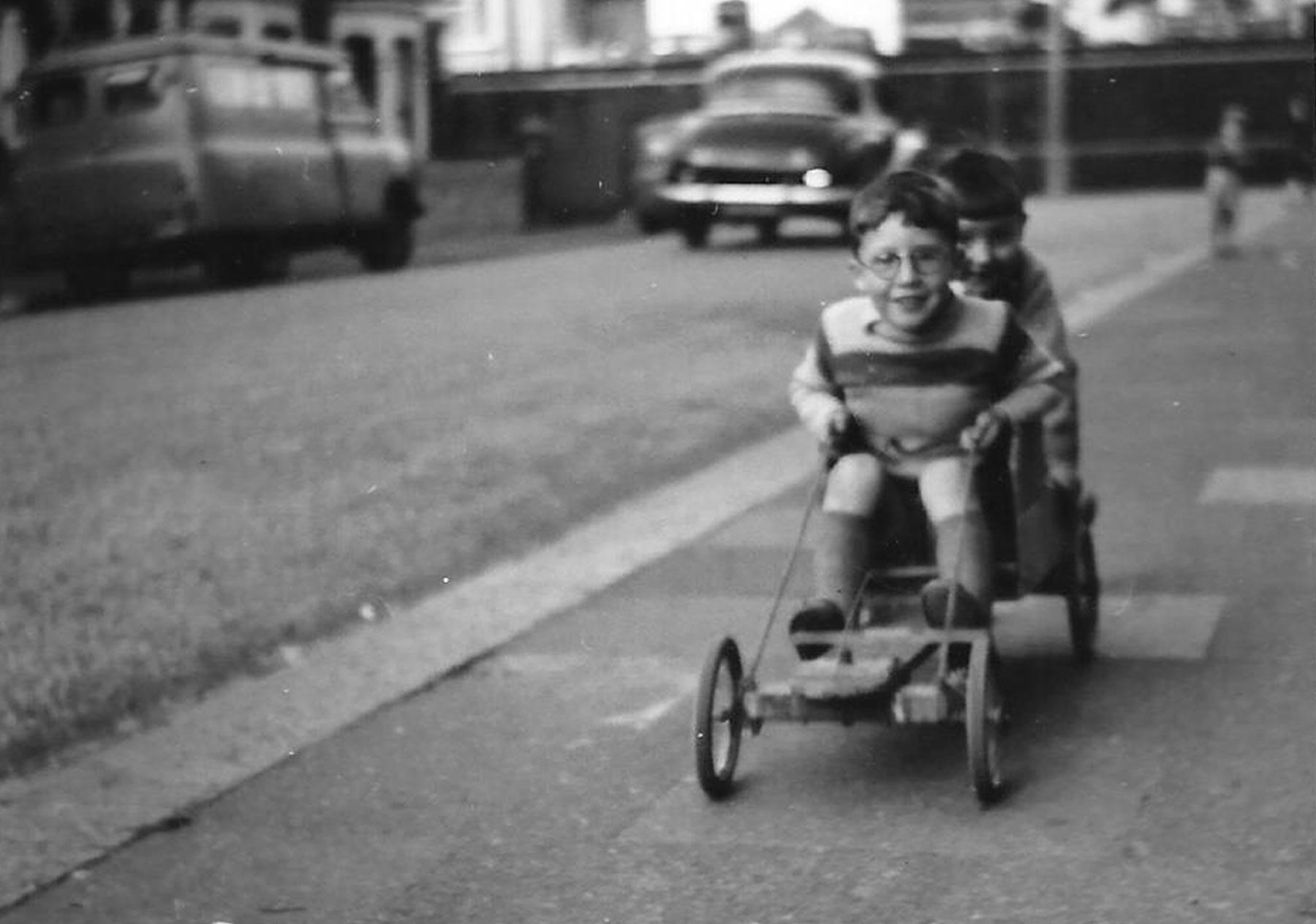 Old photo of children riding a go cart in the street