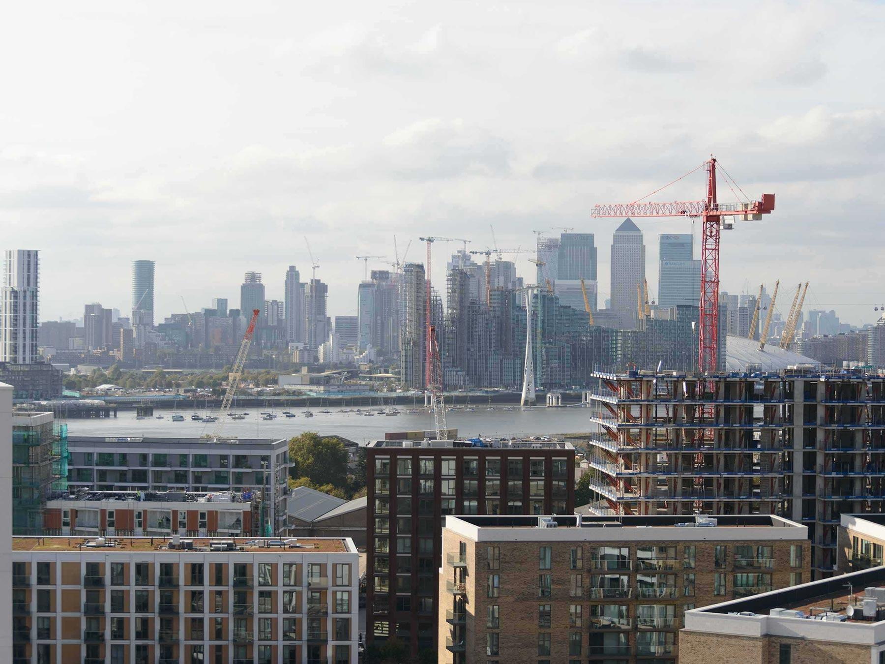 Modern day scene of buildings, cranes and the Canary Wharf skyline in the distance