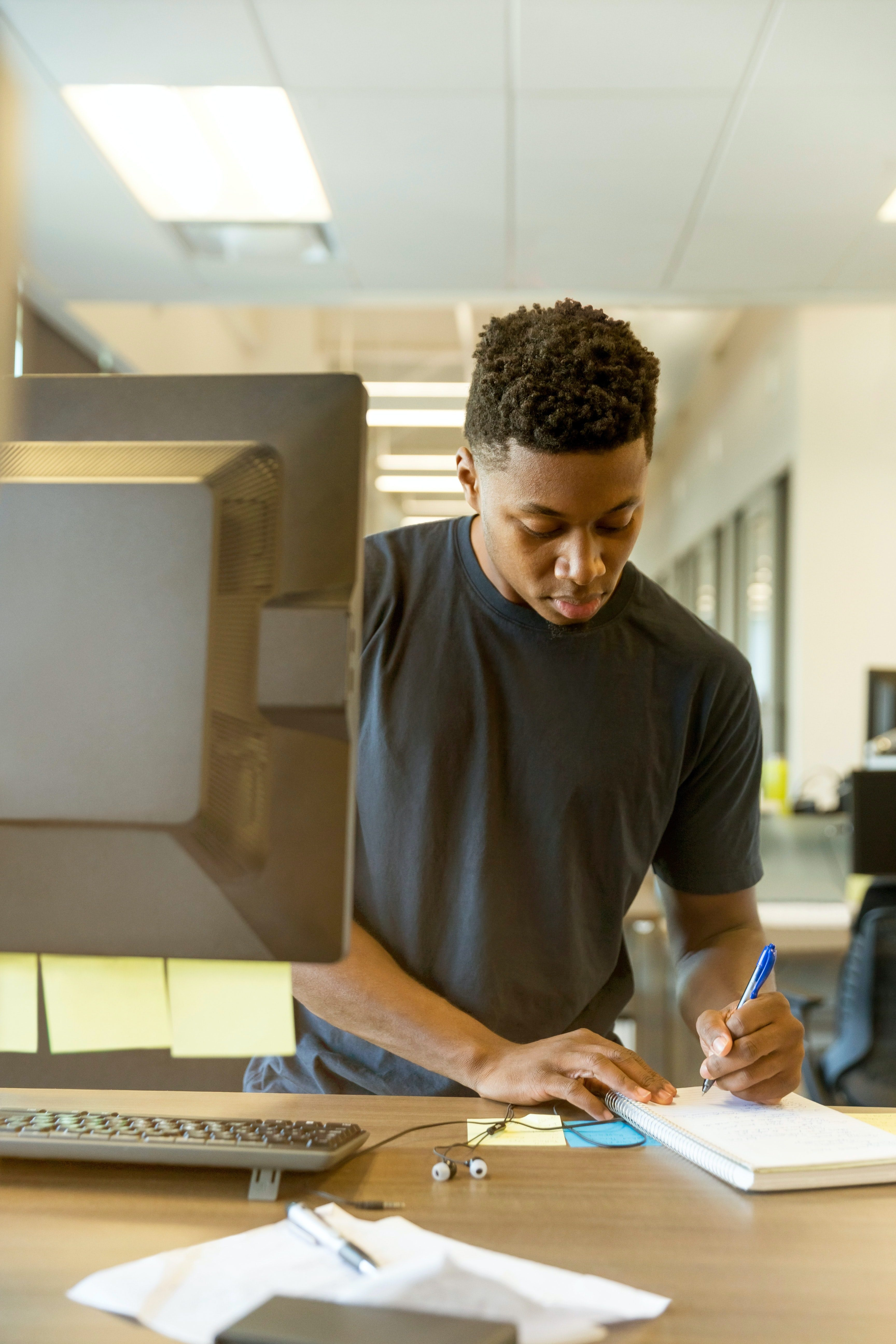 Man making notes by computer