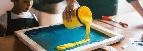 A yellow pot of paint being poured on a board
