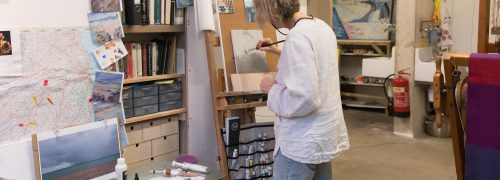 Artist in a studio painting at an easel