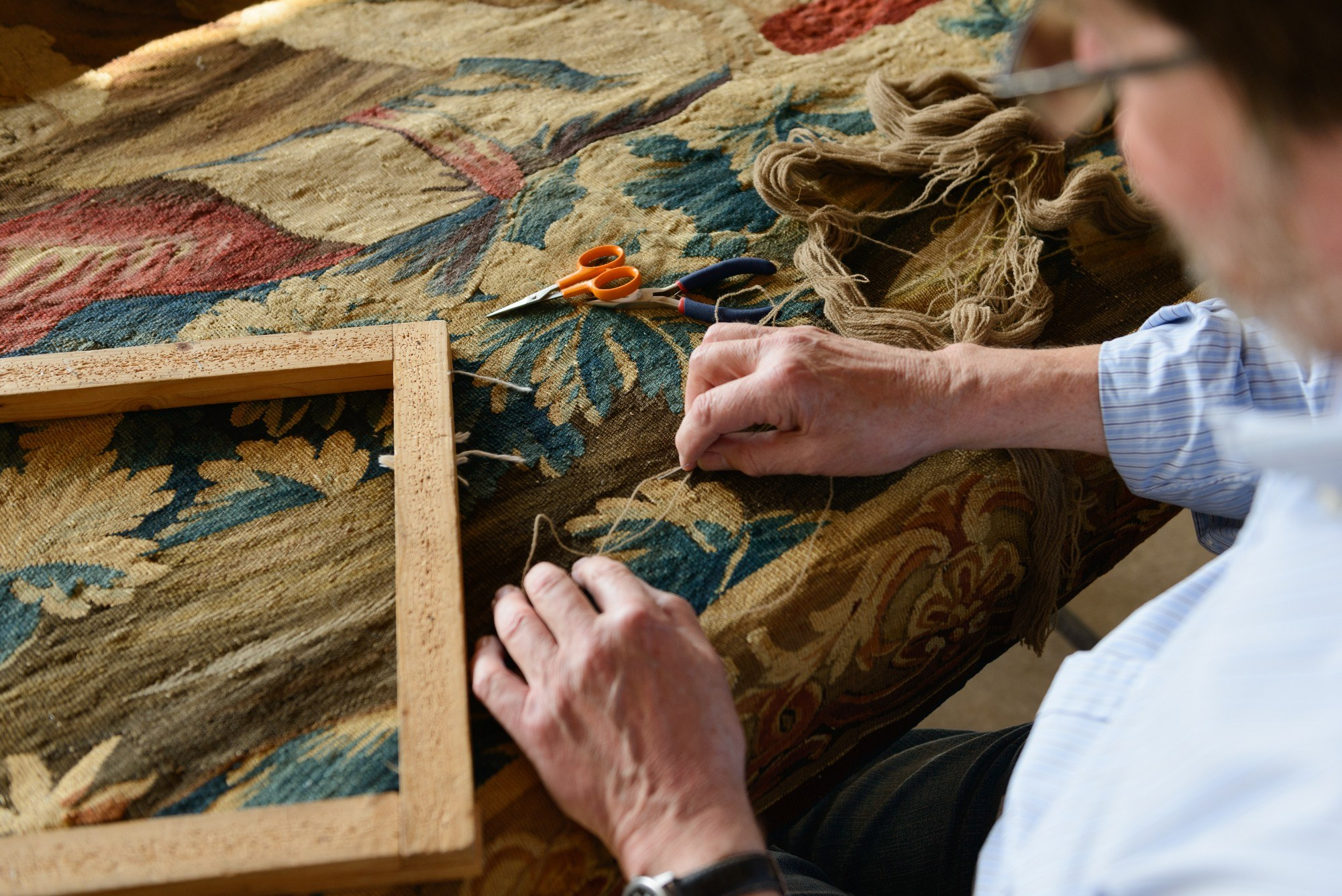 Man working on a tapestry