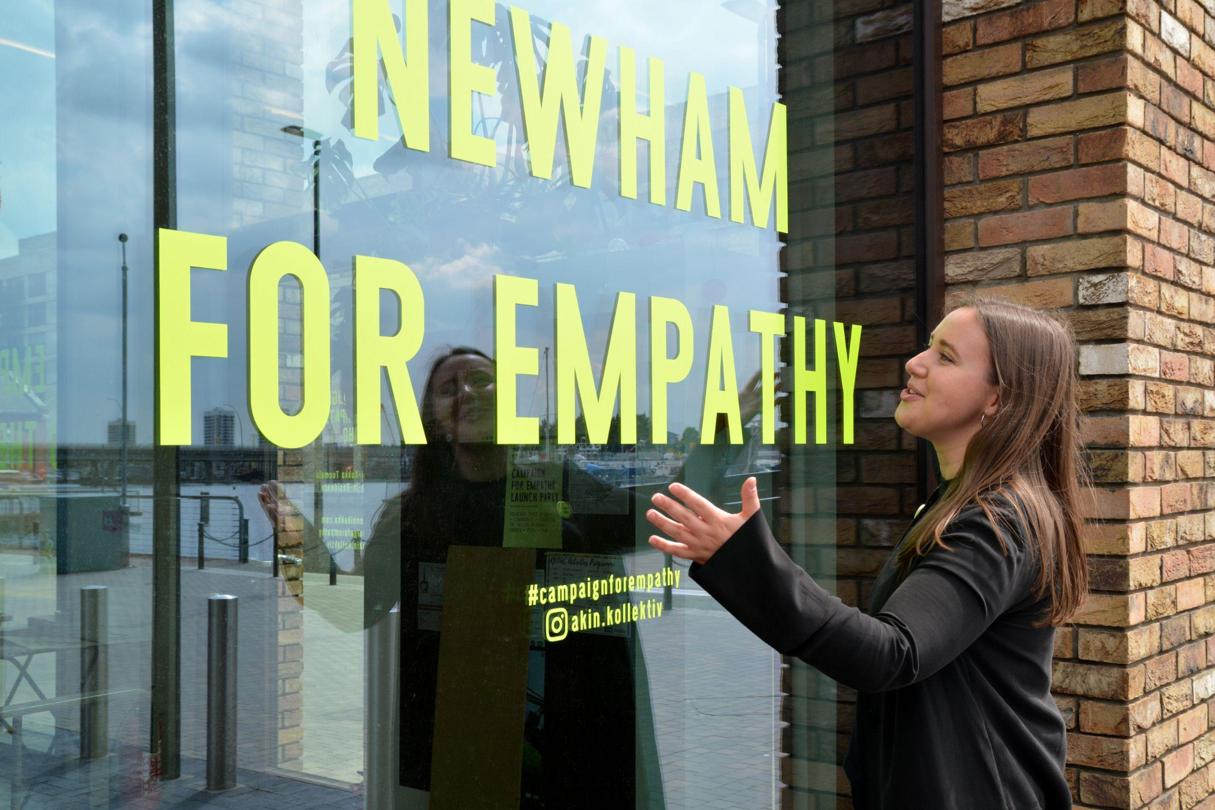 Enni-Kukka Tuomala in front of Newham For Empathy window sign
