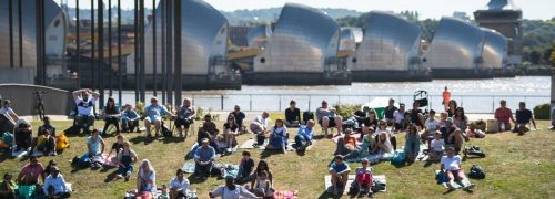 Image shows people sitting on the grass at Thames Barrier Park, enjoying an event.
