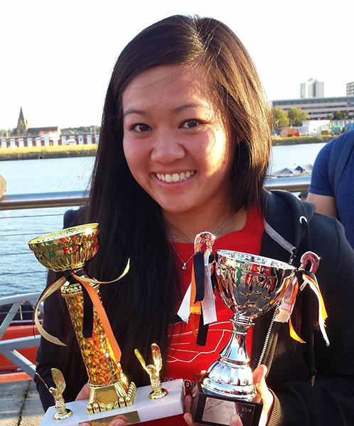 Cheryl Phan holding two trophies