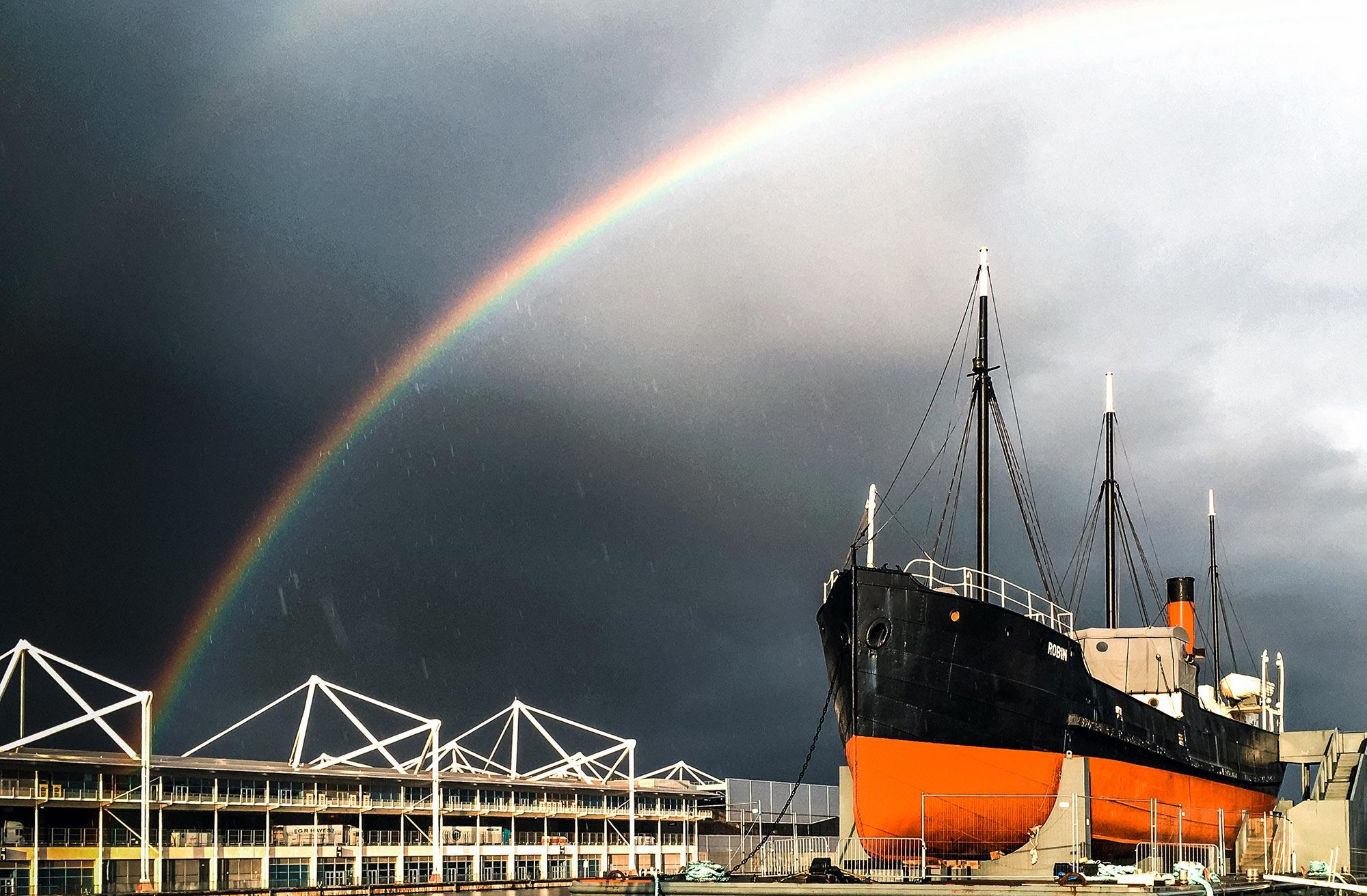 SS Robin in the Royal Docks with a rainbow in the sky