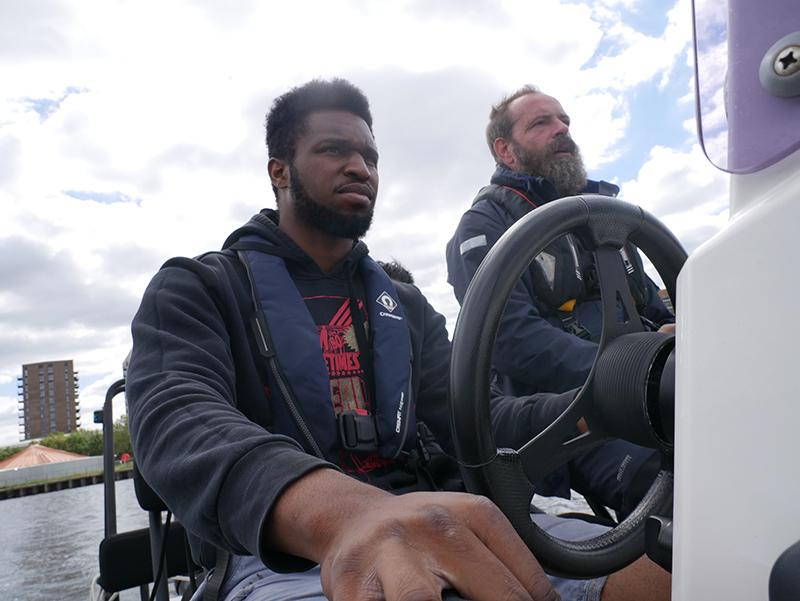 Tyrone Ferguson steering a boat in the Royal Docks