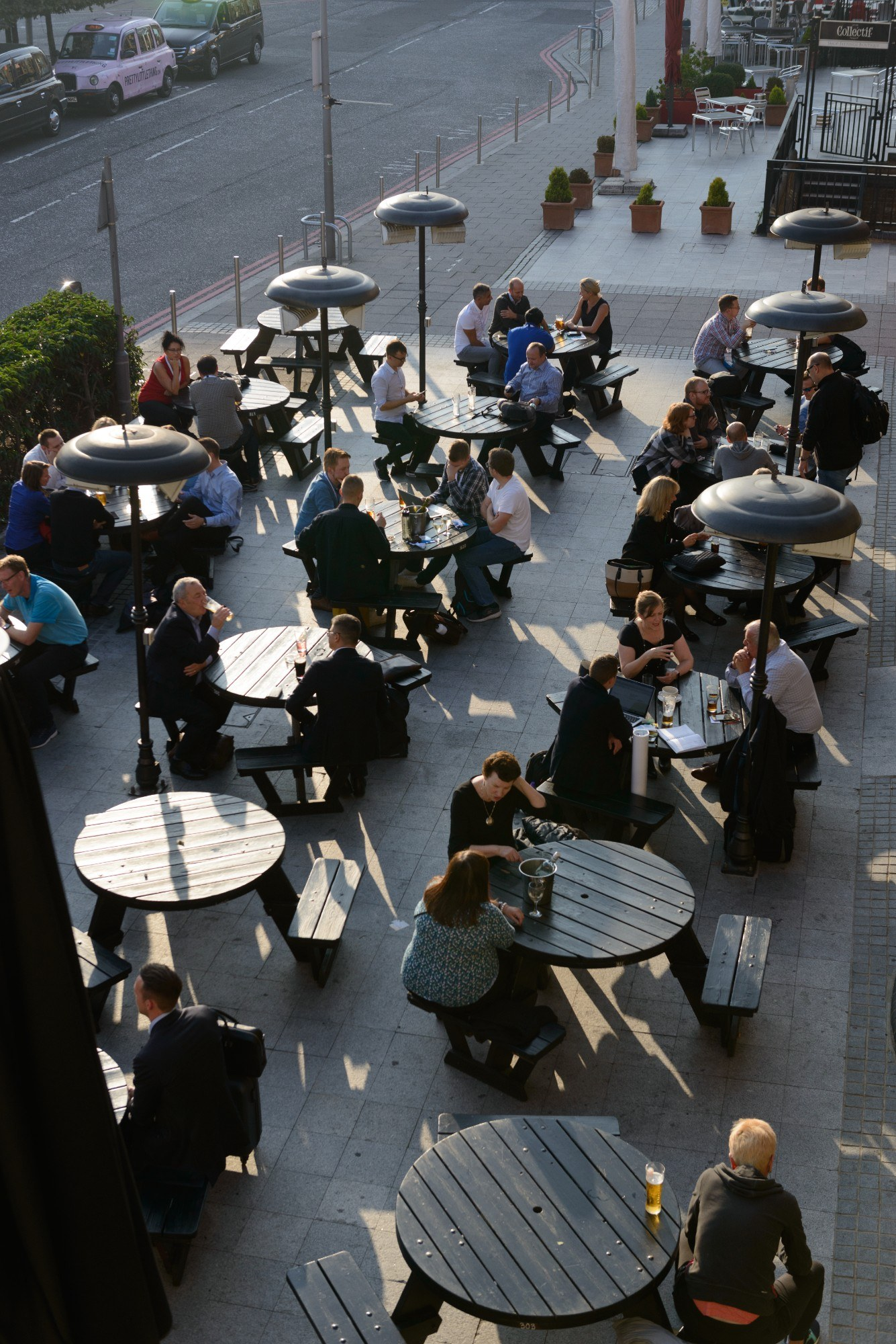 People sat at tables outdoors near ExCeL