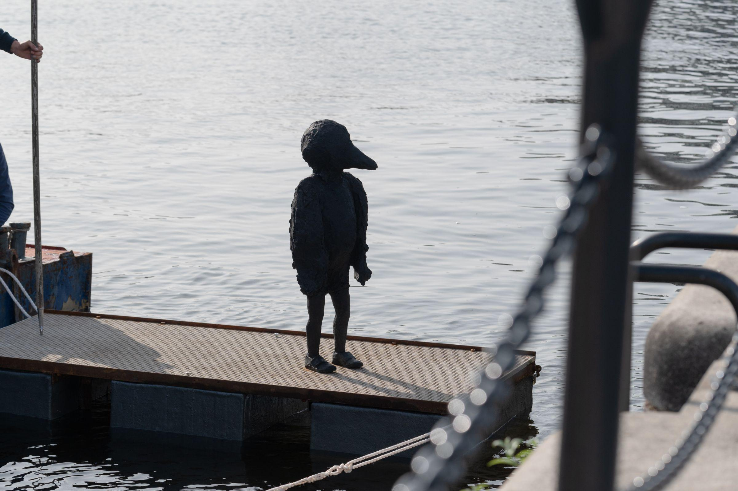 Statue that looks like a child with a bird's head, floating on a platform in the dock