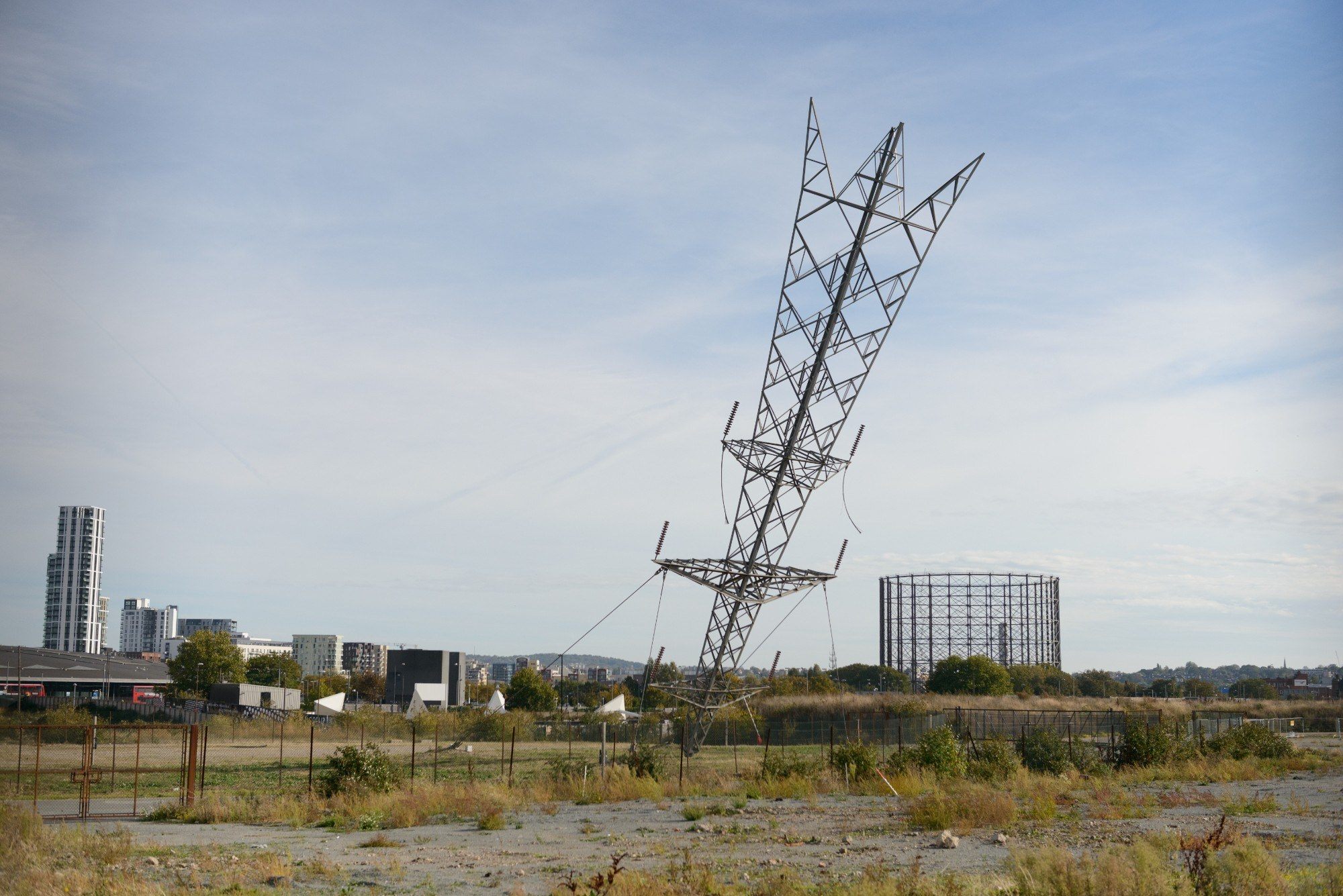 Sculpture that appears to be an electricity pylon that has crashed landed into the earth head first