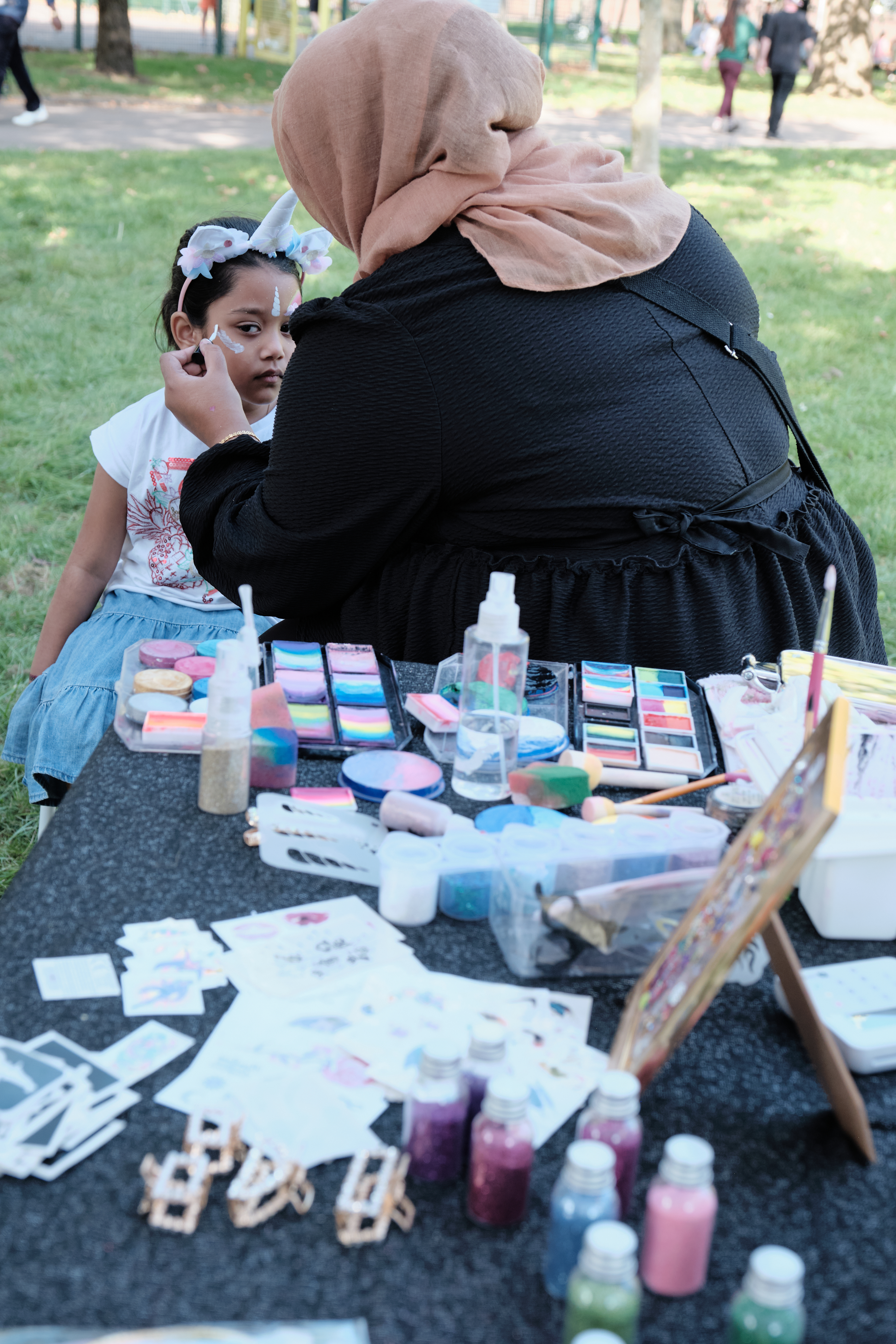 Young girl is face painted by artist