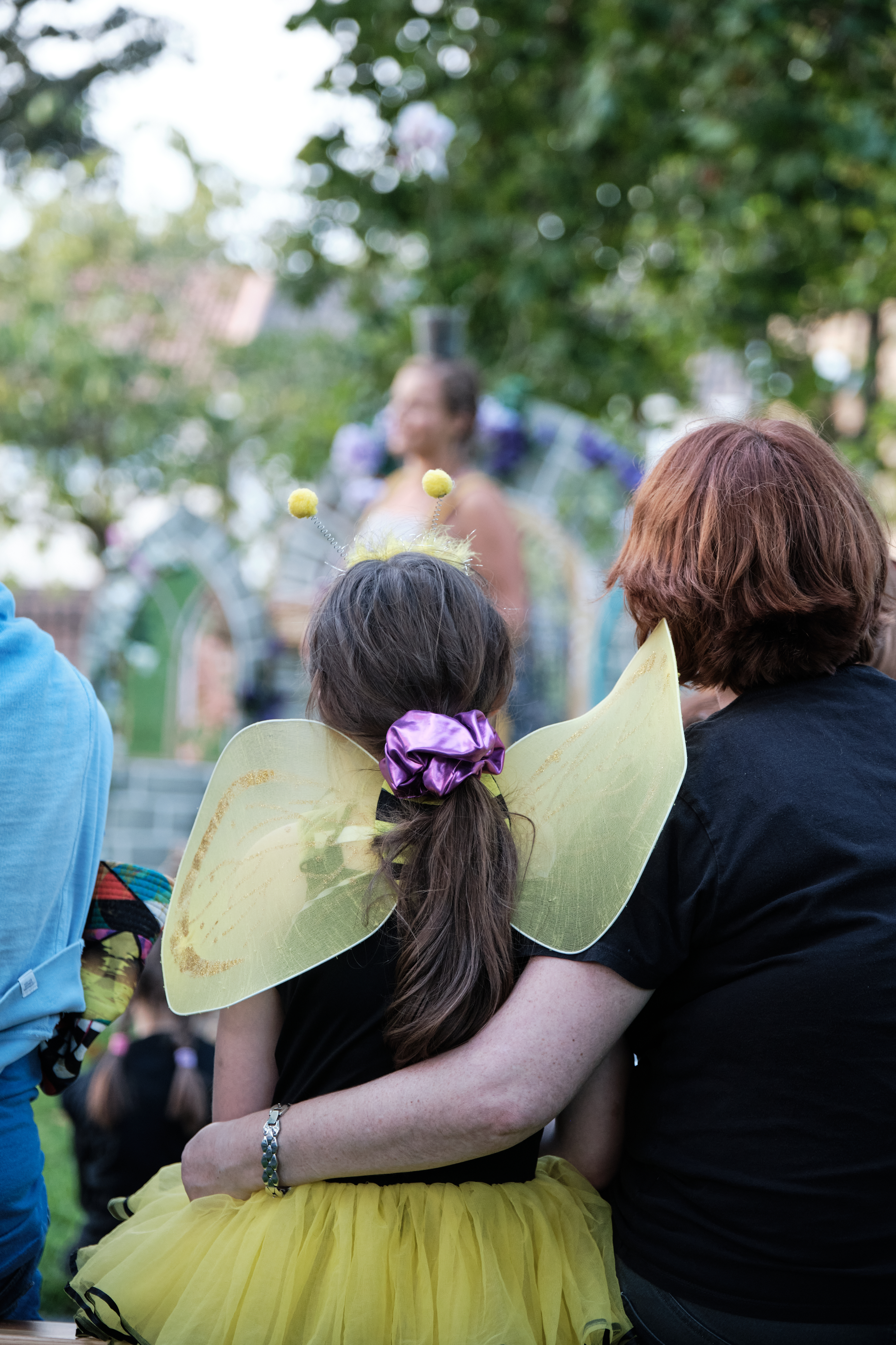 Girl in bee costume sits in audience with mother