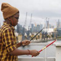 Child using drum sticks on railing at the Royal Docks