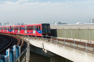 DLR train travelling along the tracks in the Royal Docks