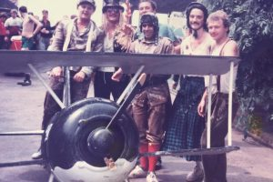 Group of men in unusual costumes standing behind a large model plane