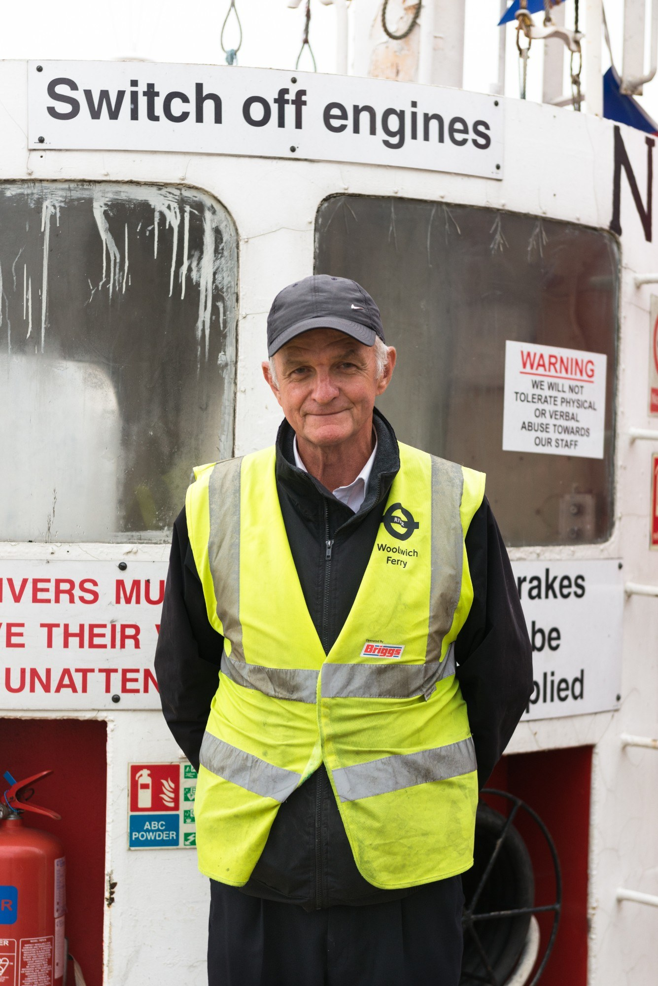 "Portrait of ferry operator, with sign saying ""switch off engines"""