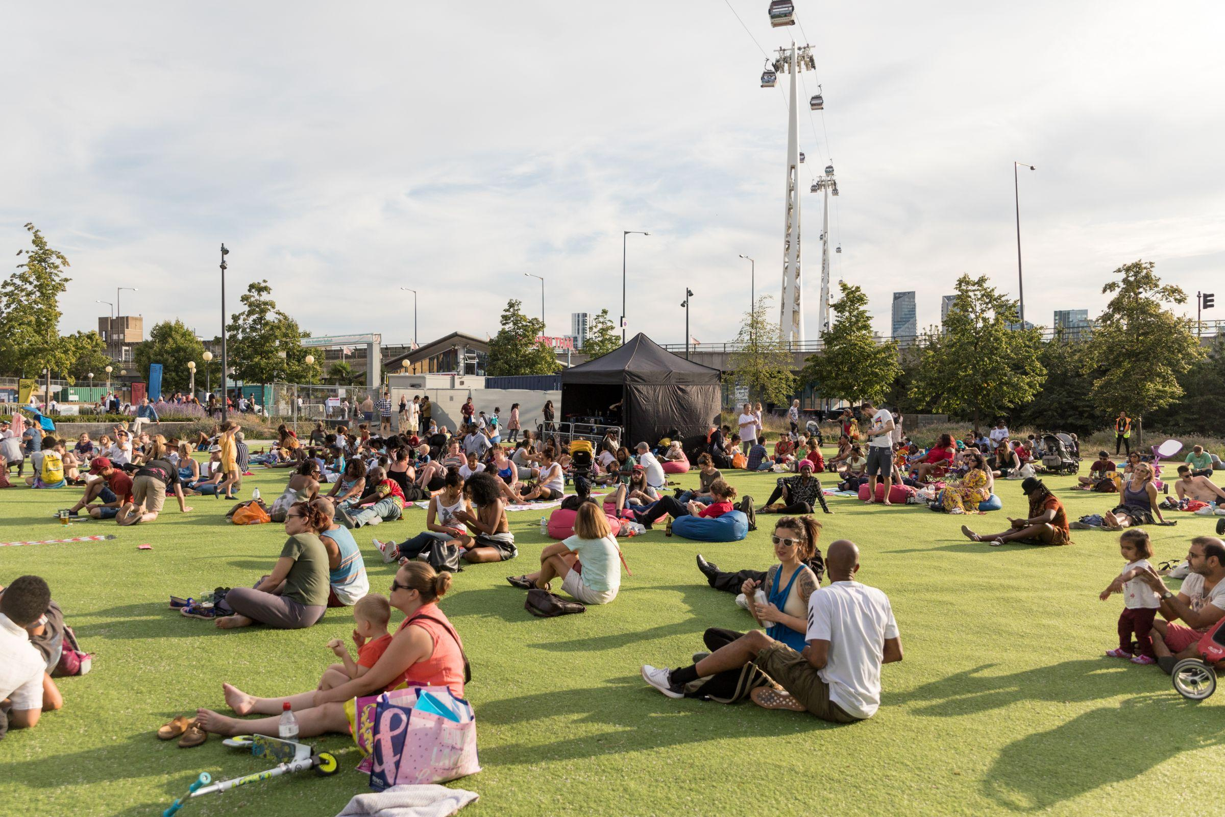 A large crowd sat on grass in the sunshine