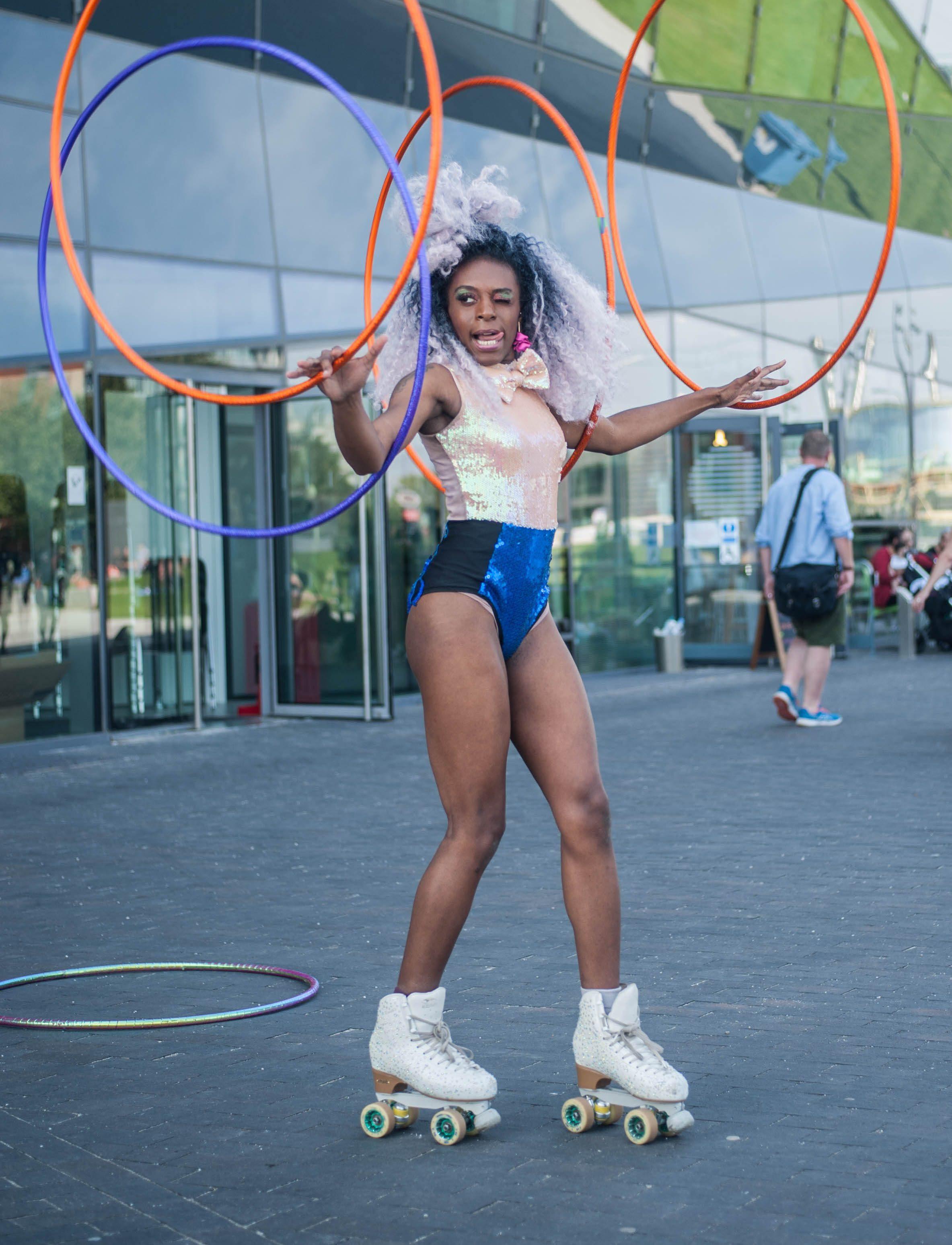 A woman wearing rollerskates carrying hula hoops
