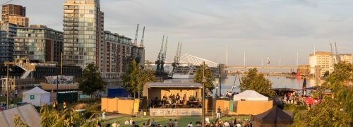 A crowd watching a band perform with the Emirates Cable Car overhead