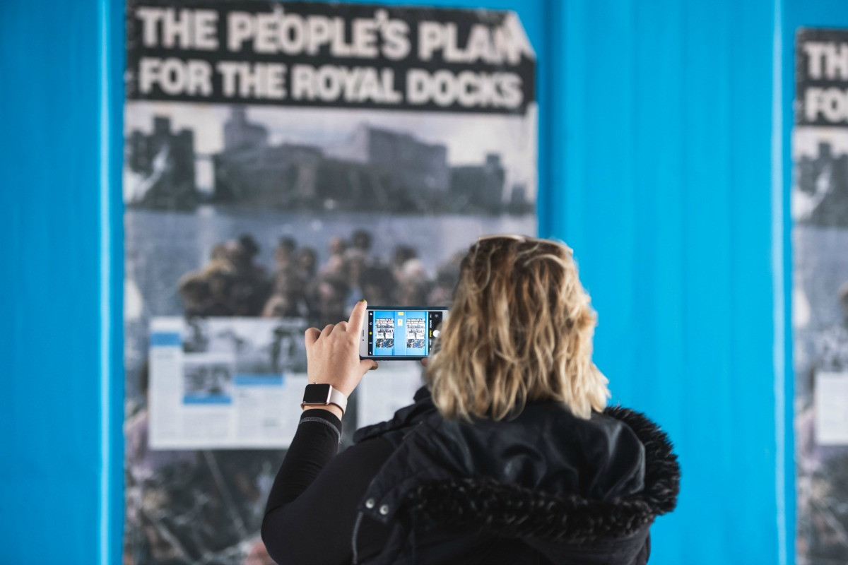A woman taking a photo of The People's Plan for the Royal Docks