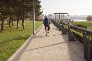 Cyclist in Thames Barrier park with text on ground reading 'please keep four gulls apart'
