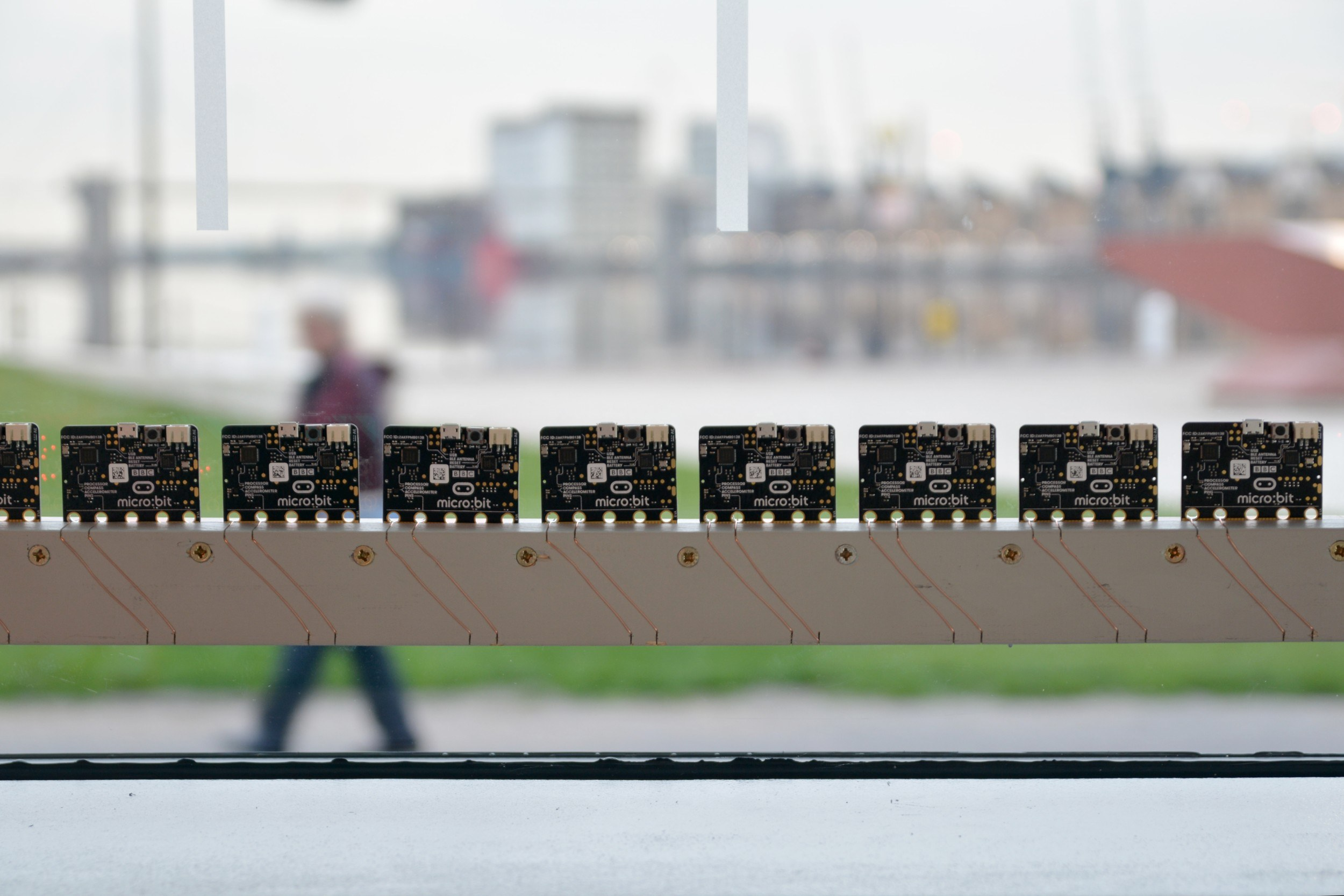 Photo of the backs of a row of multiple LED lights with the Royal Docks in the background