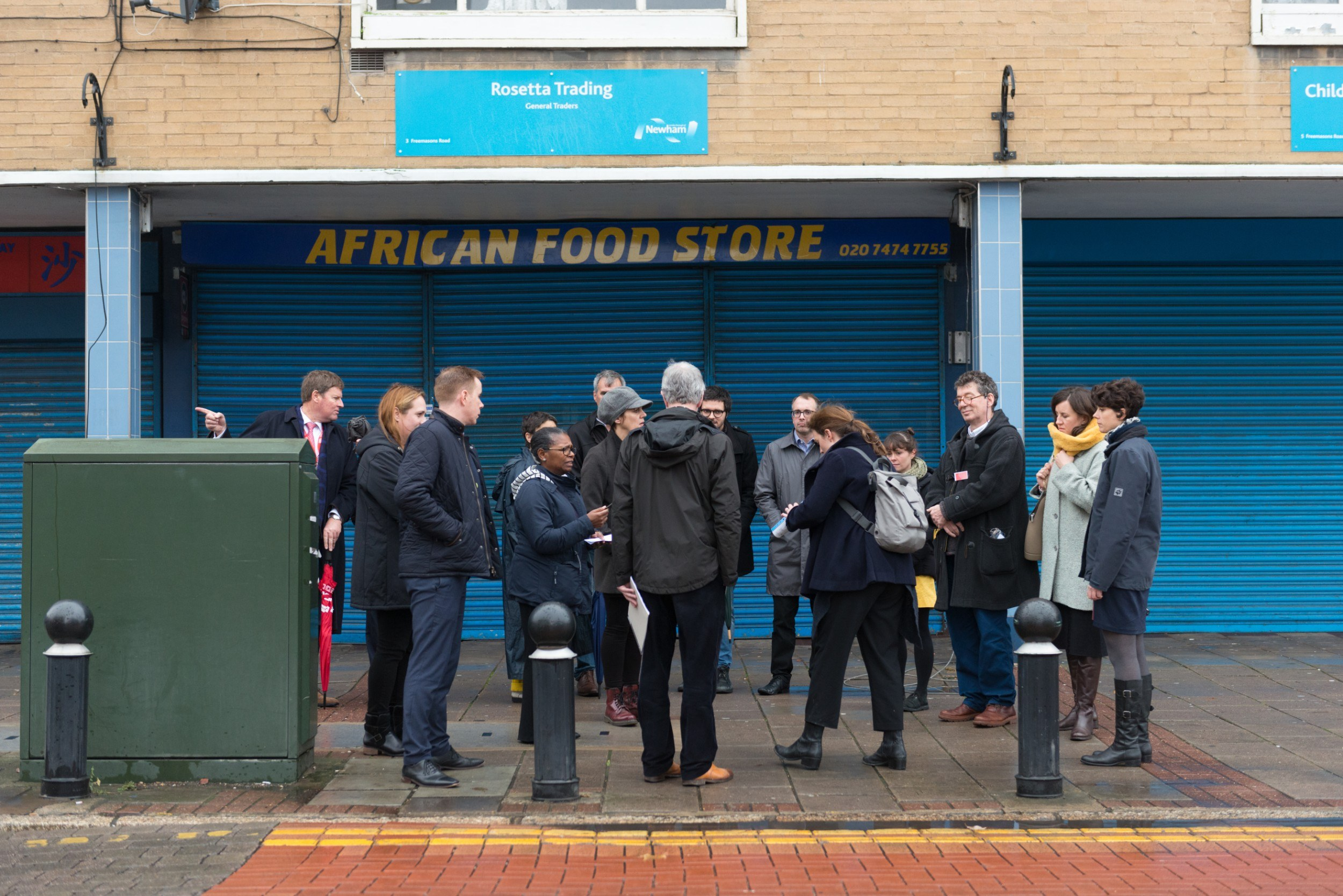 Group of people standing outside a shuttered shopfront
