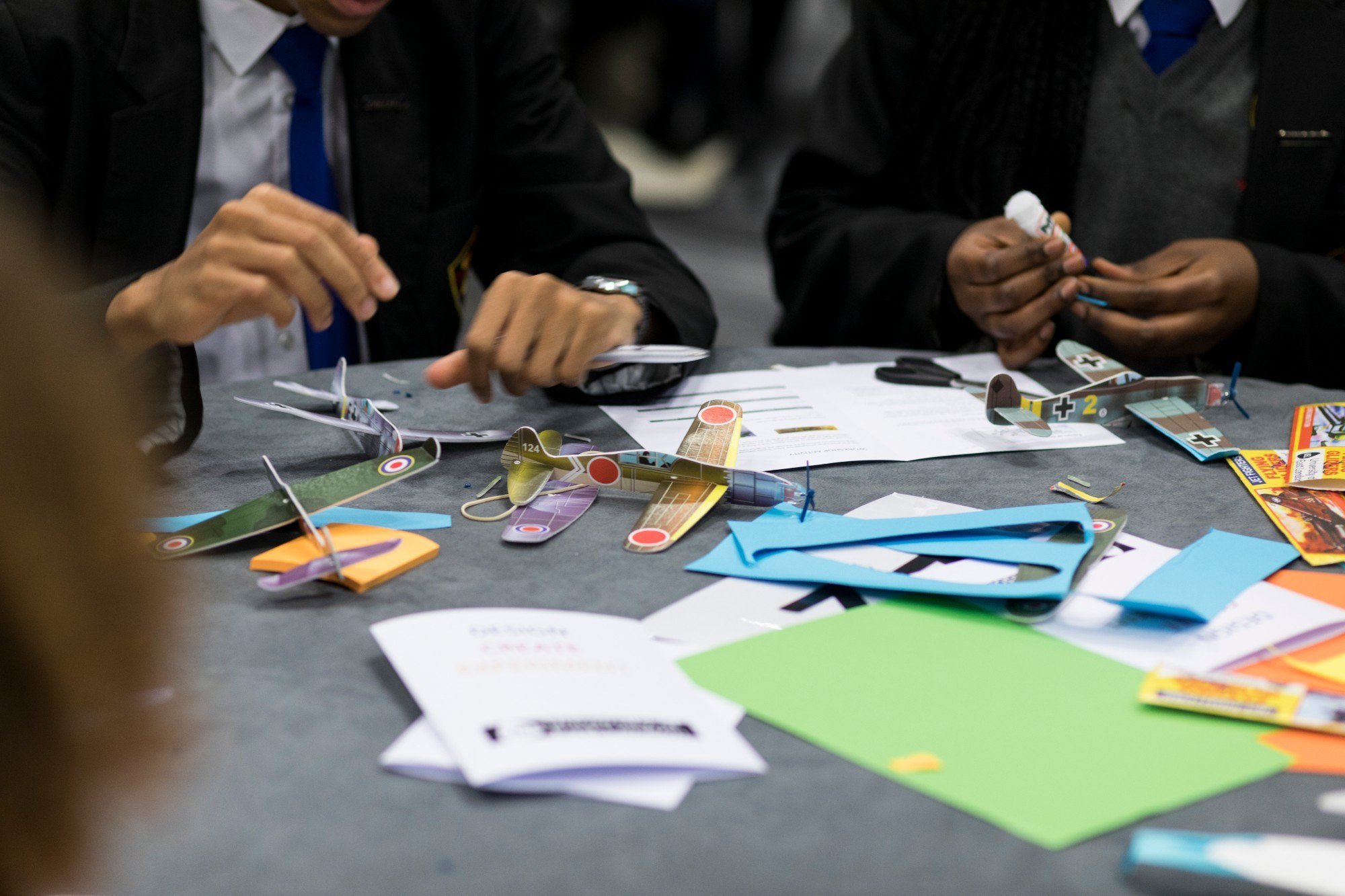 Small model planes and coloured paper on a table, with children working on them