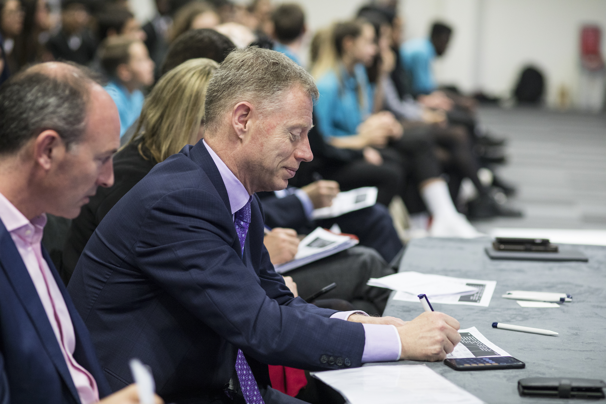 LCY CEO Robert Sinclair sitting on a judging panel, with a slight smile on his face making notes