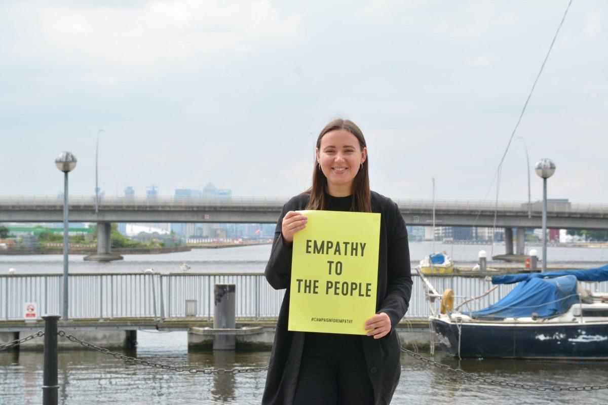 Artist Enni-Kukka Tuomala holding an 'Empathy To The People' sign