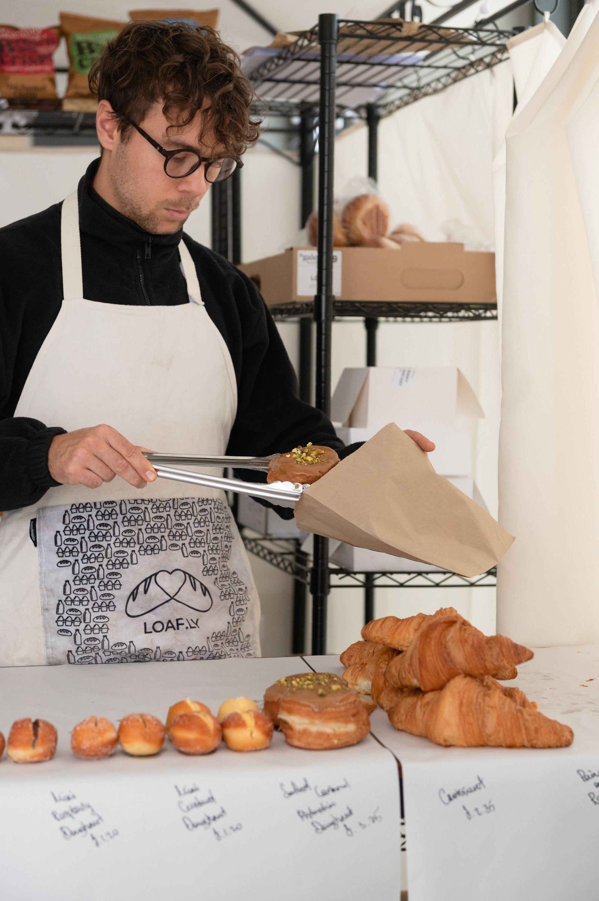 Pastries being put in a bag by a loafly employee