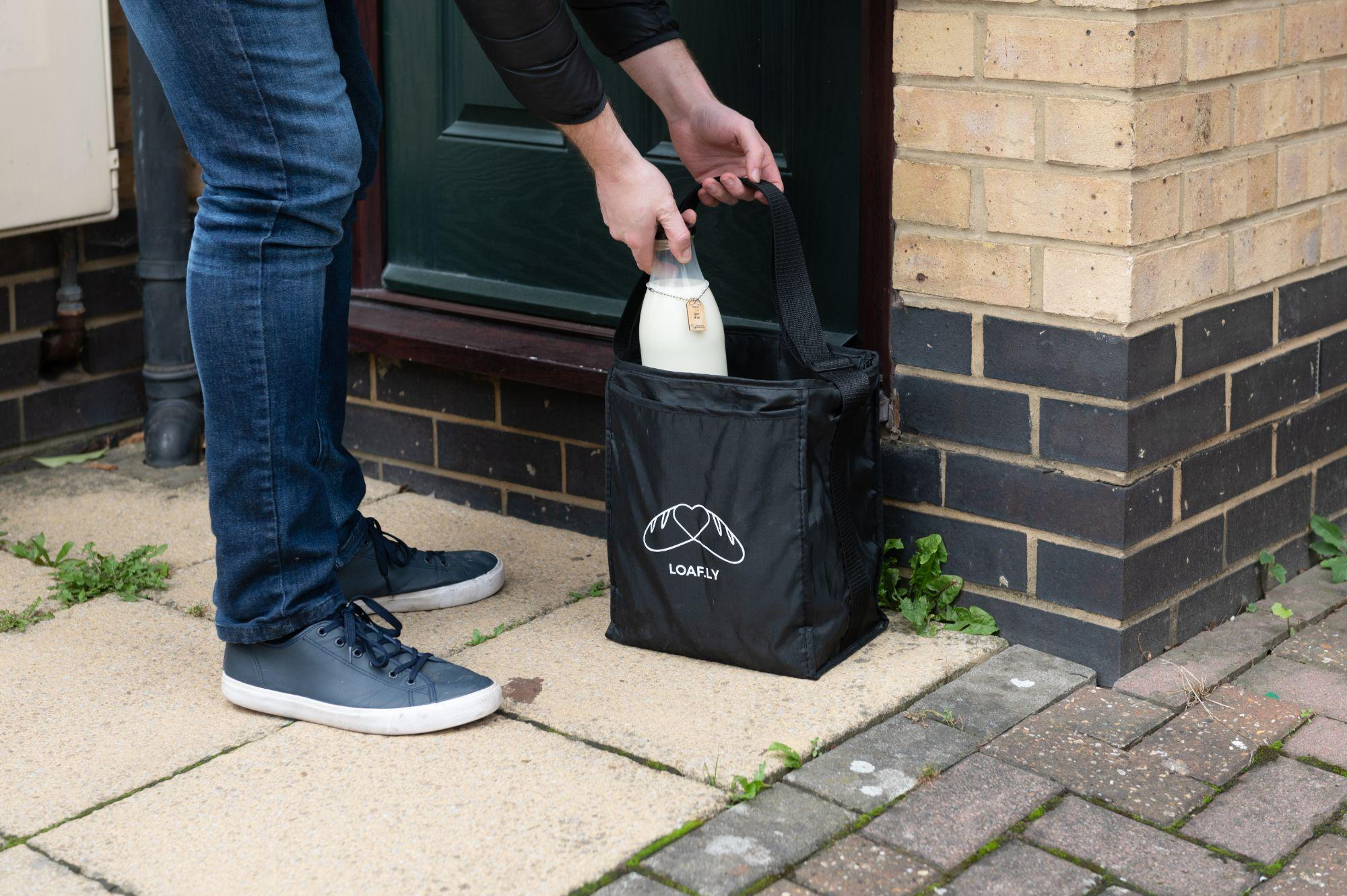 A bottle of milk being lowered into a loafly delivery bag