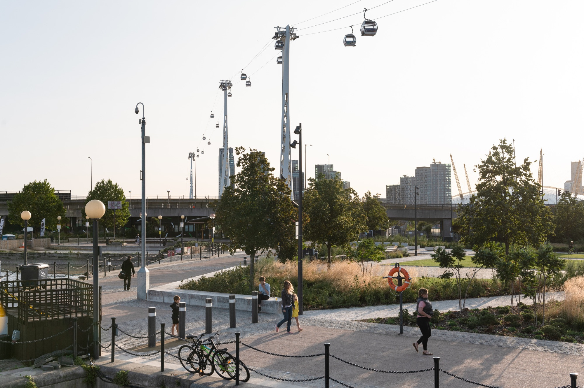 Sunset scene next to Royal Victoria Dock, with gardens and the cable car running overhead