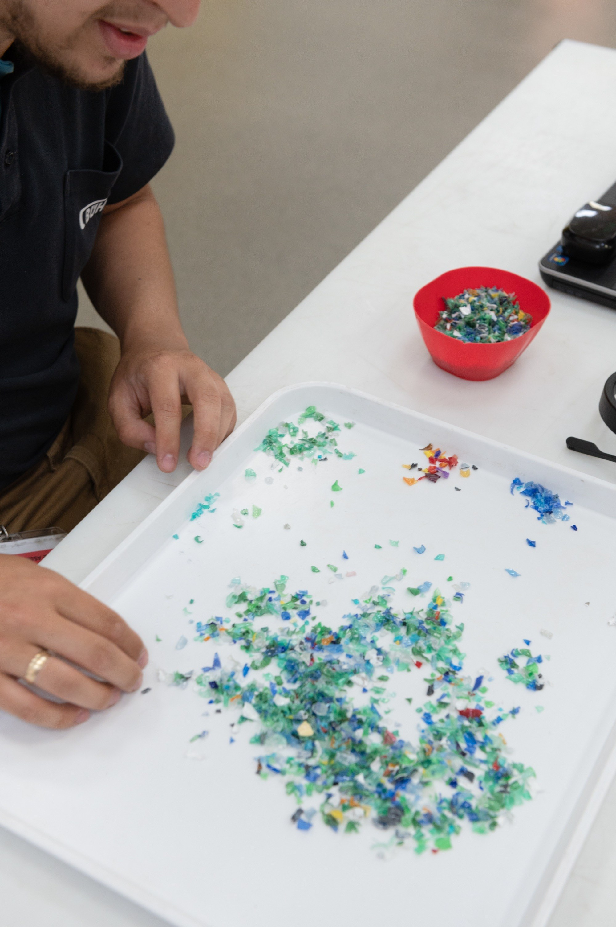 Buhler in the Royal Docks, man sorting tiny pieces of plastic at a desk