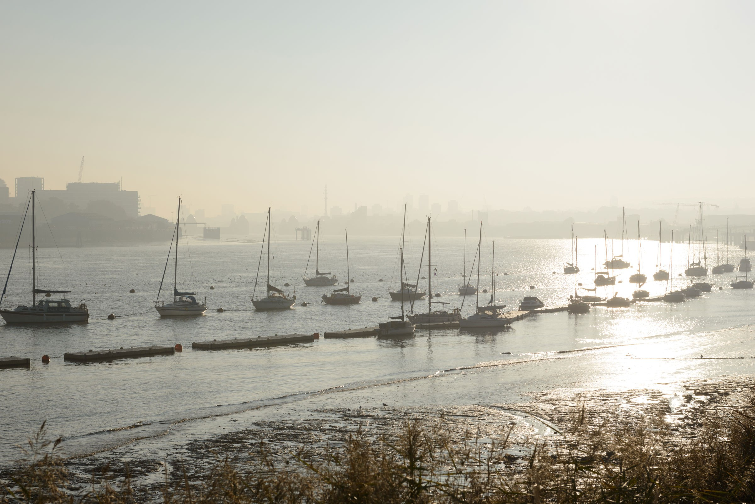 Boats in the Thames off the Royal Docks in hazy sun