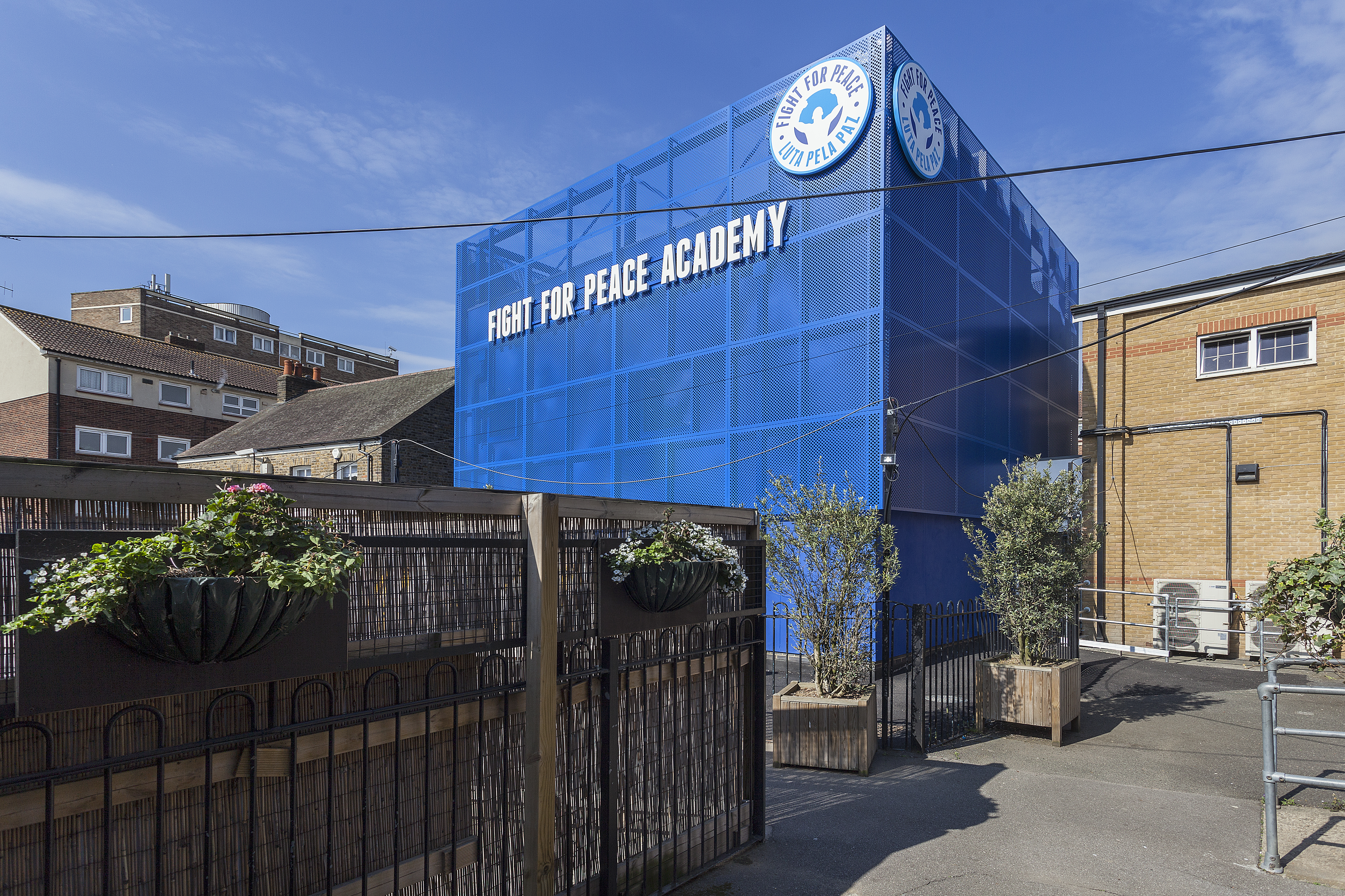 Striking blue building a few storeys high that says Fight for Peace academy on it