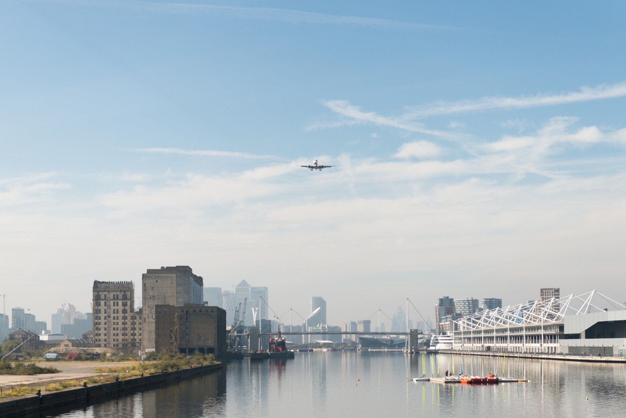 Plane in the sky having departed London City Airport with Canary Wharf in the background