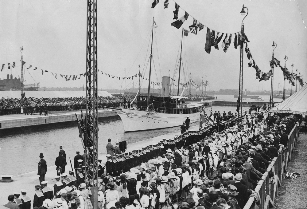 Dock lined with flags and sailors in uniform