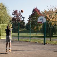Teenager playing basketball in a park