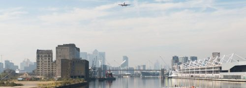 Panoramic view of the Royal Docks with a plane coming in to land