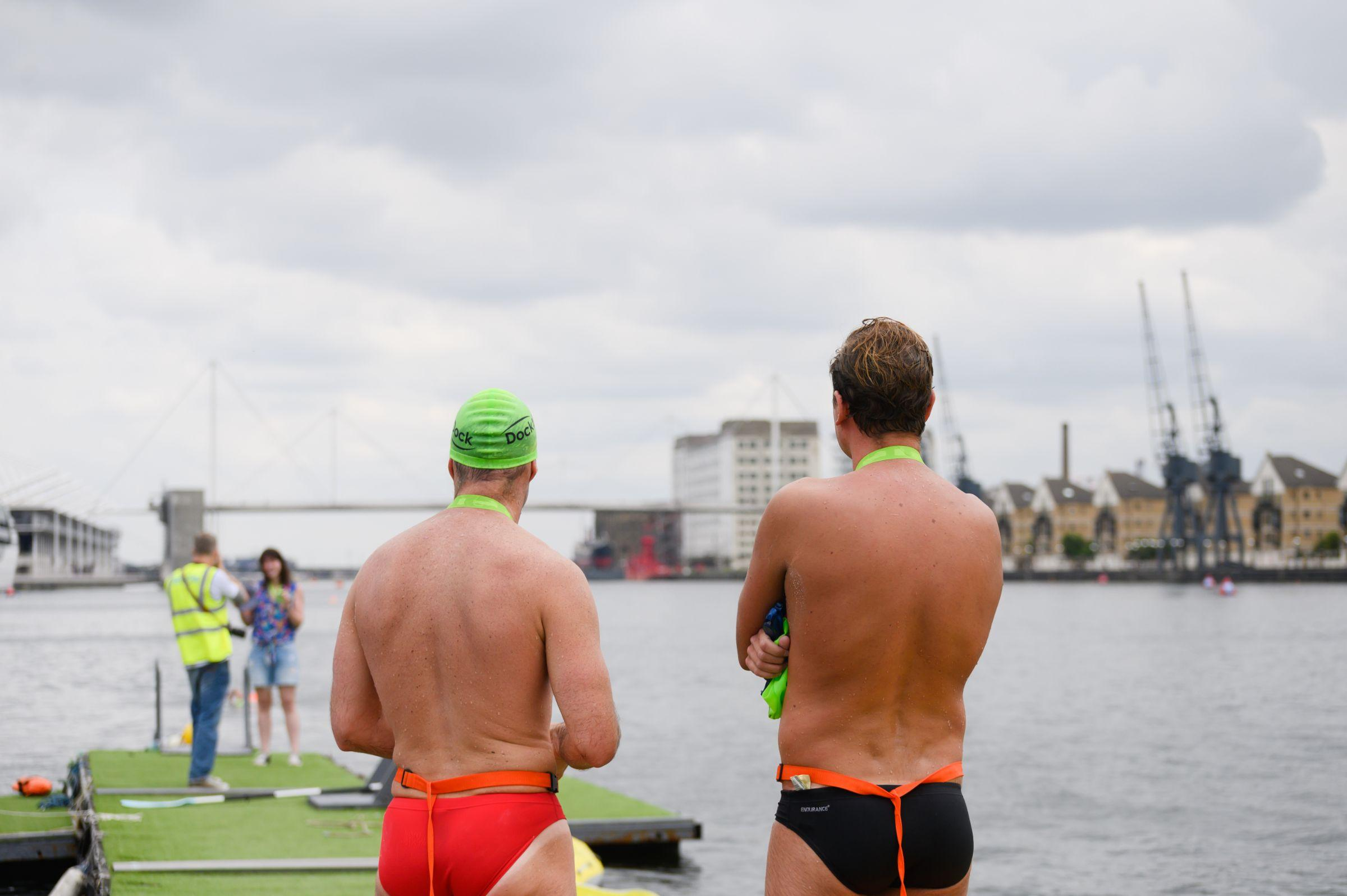Two men in swimming costumes looking out on to the water at the Royal Docks
