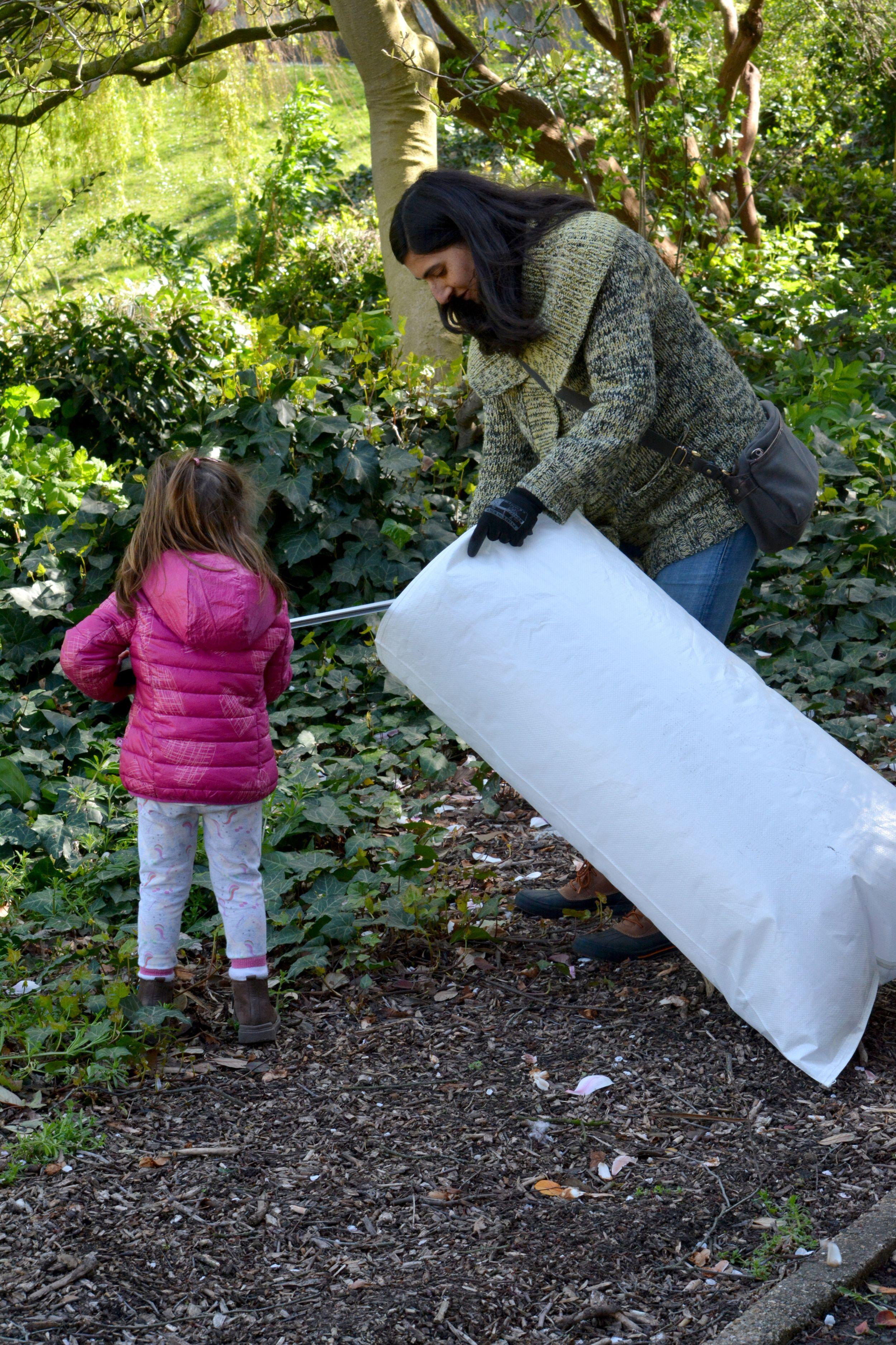 A woman and a child picking up litter in a refuse sack