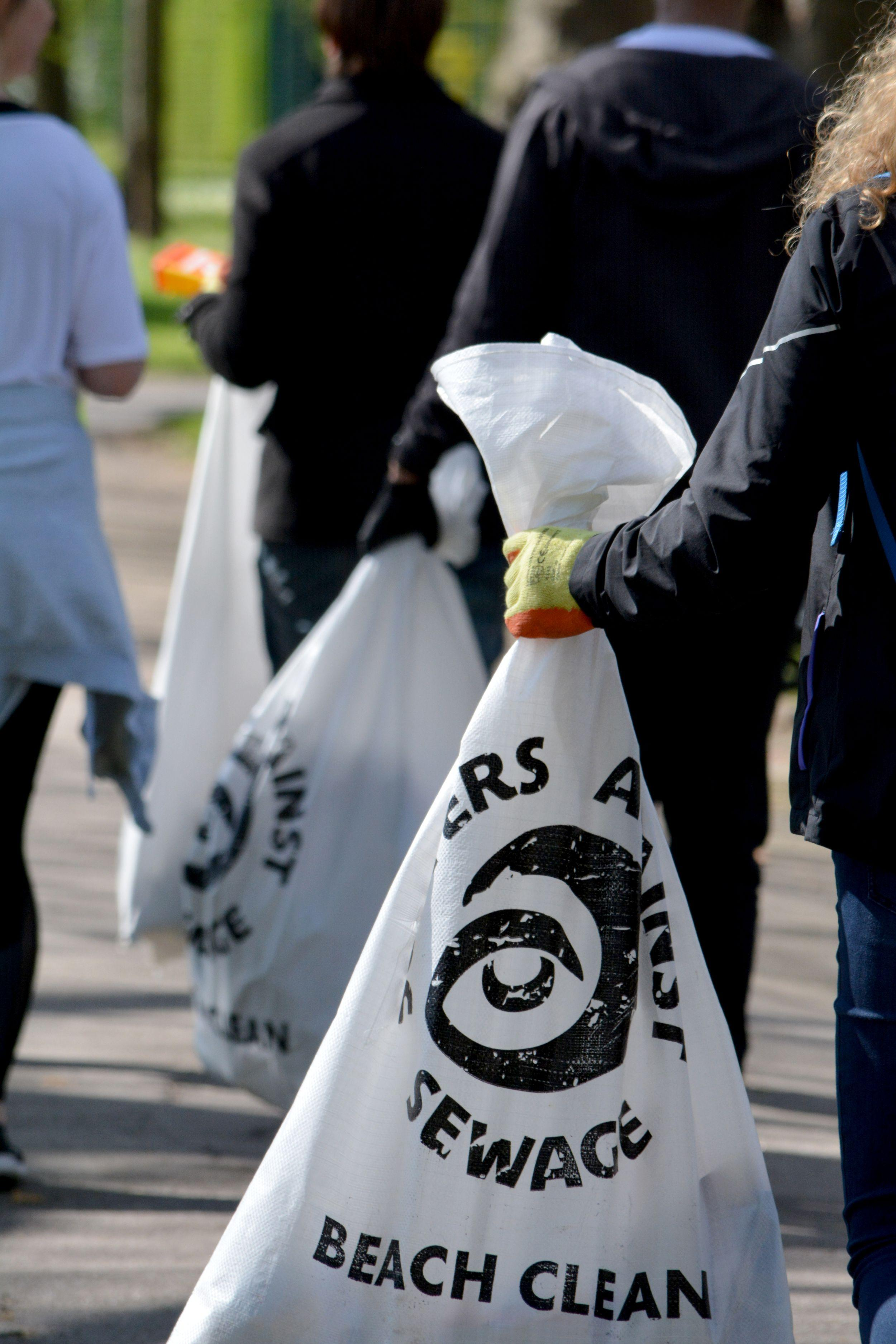 Group of people carrying refuse sacks filled with litter