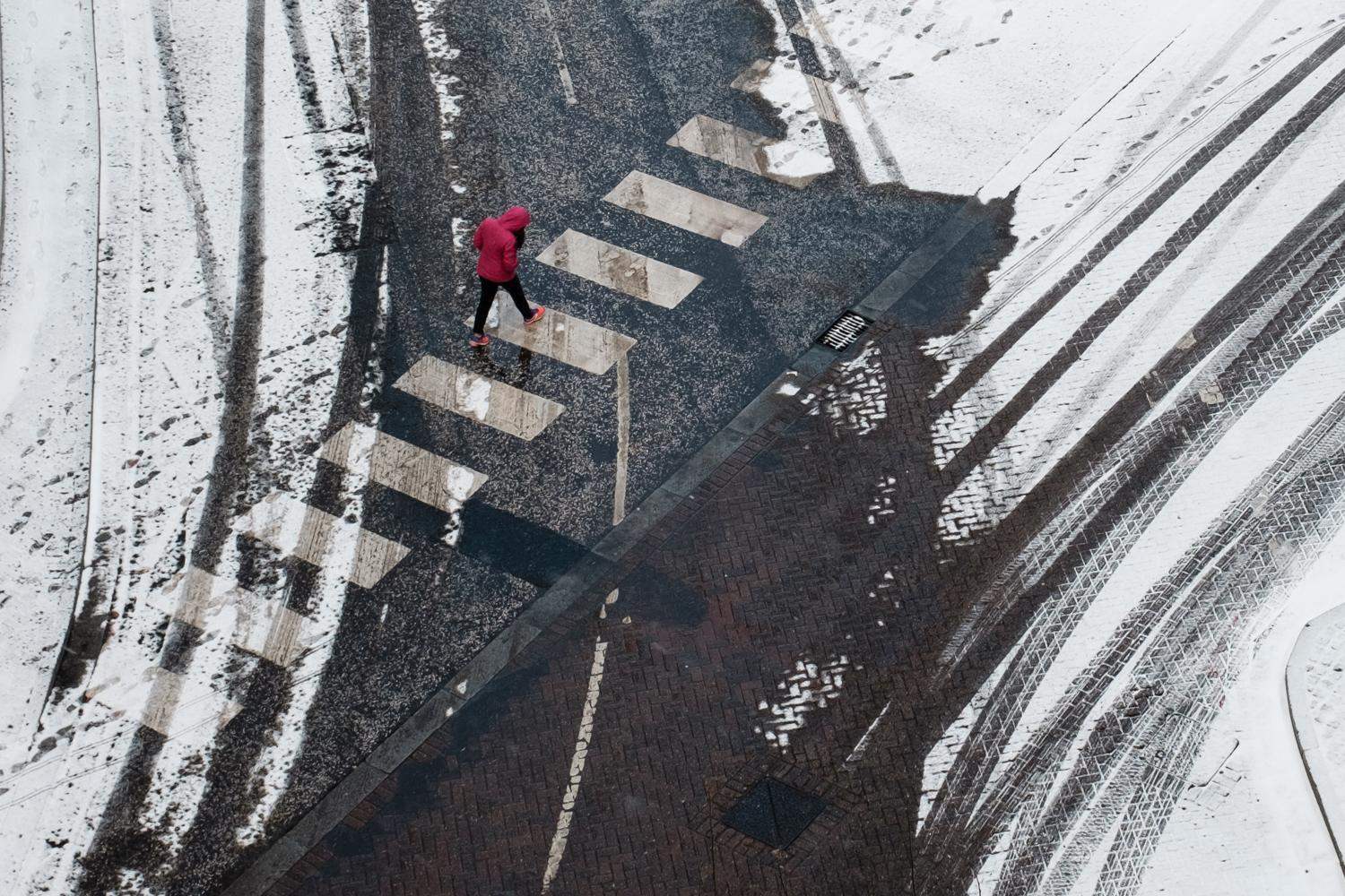 A man in a red coat crossing the road surrounded by snow