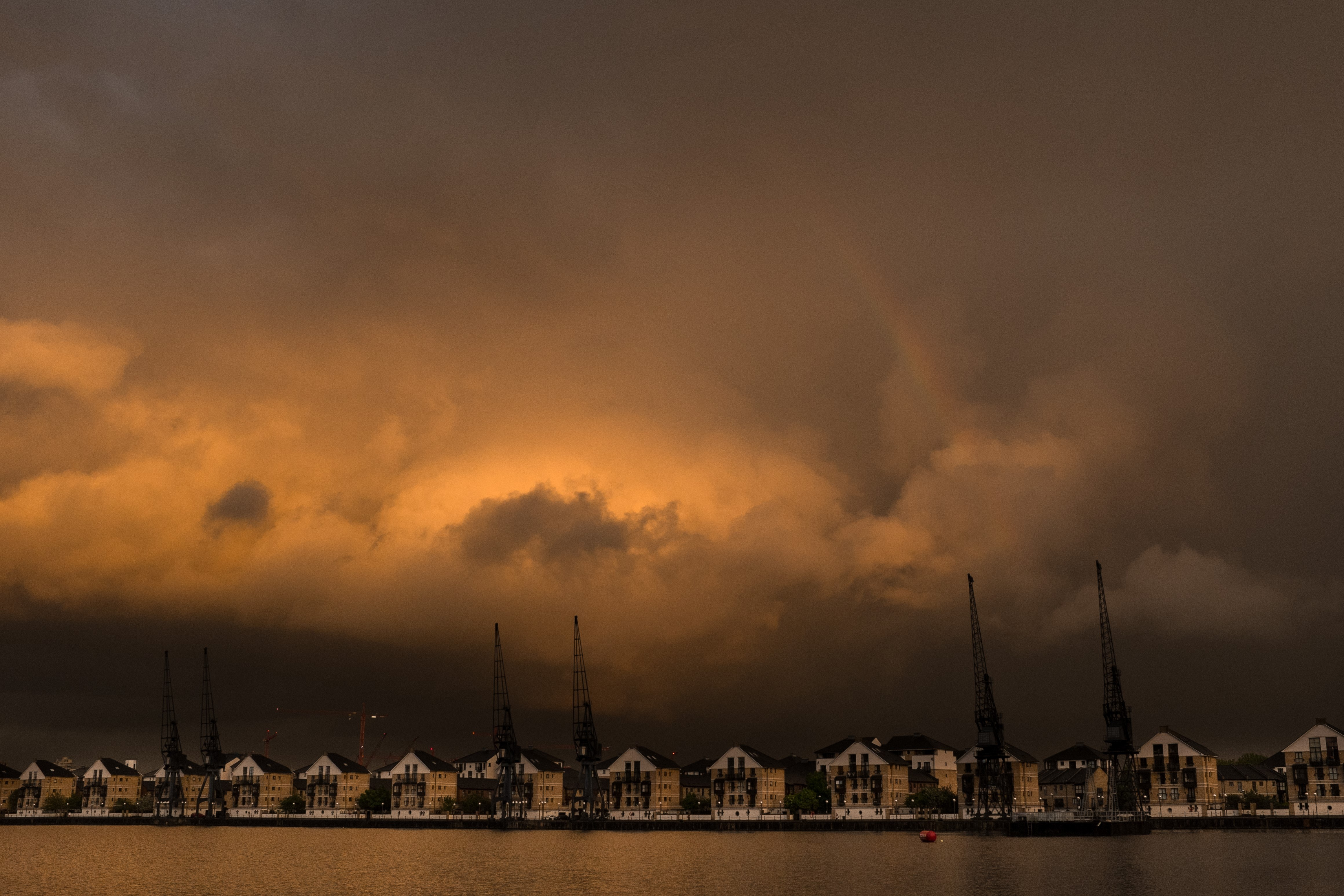A photo of buildings along the Royal Docks with a moody and dramatic skyline