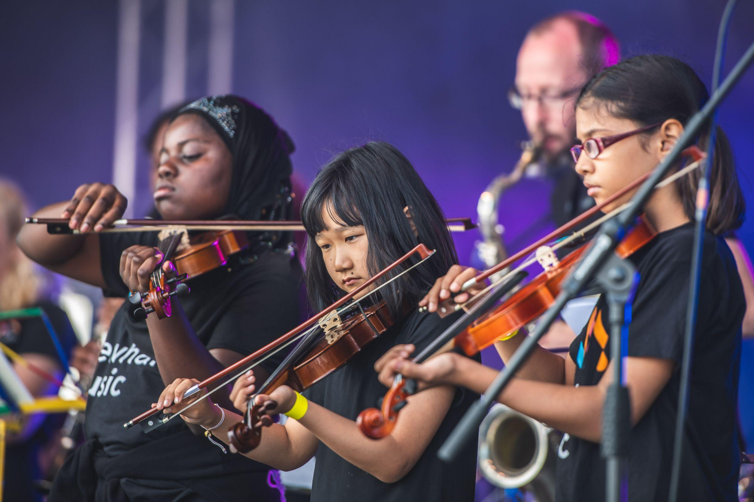 Three young performers playing the violin on stage