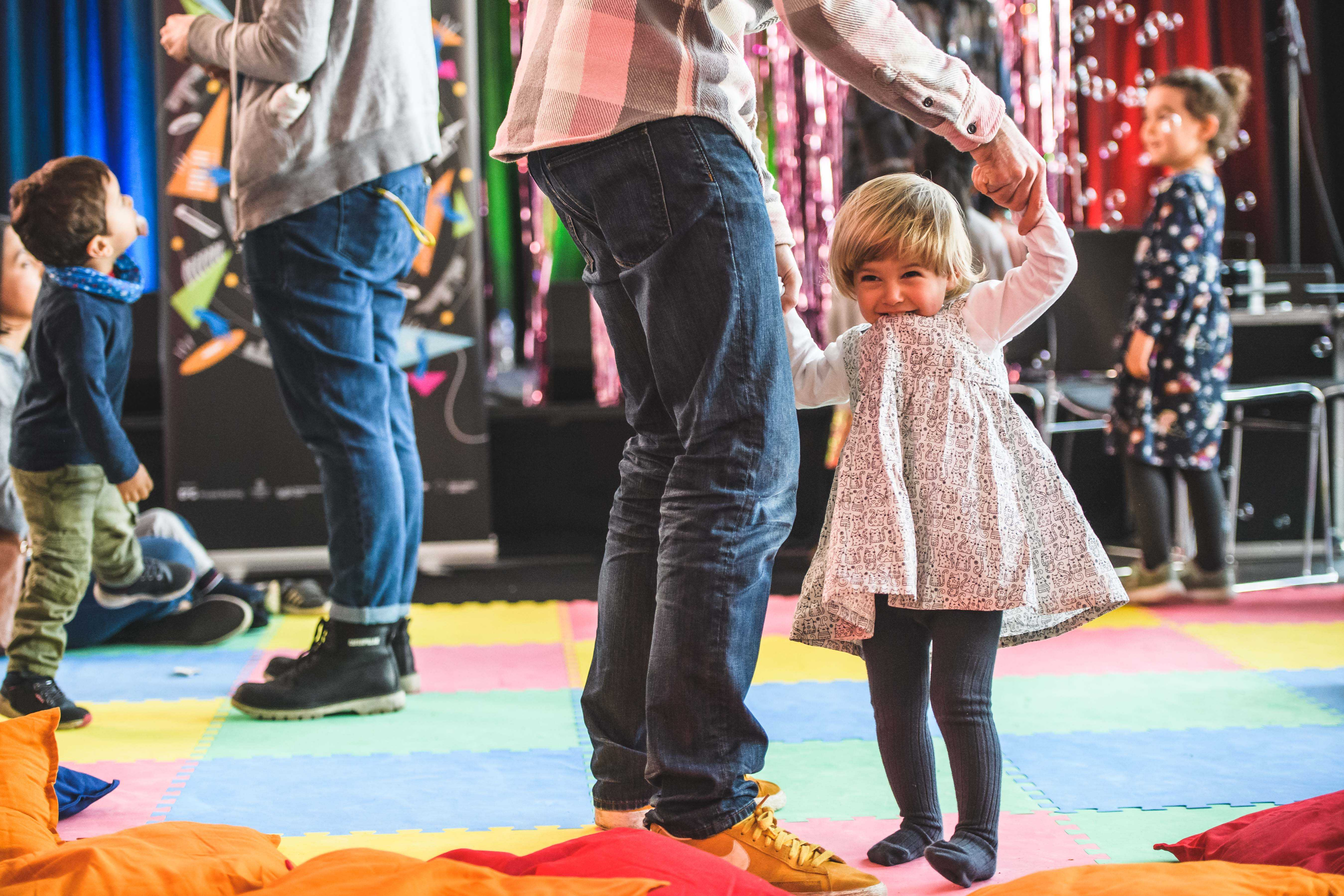 Children dancing on a bright coloured floor