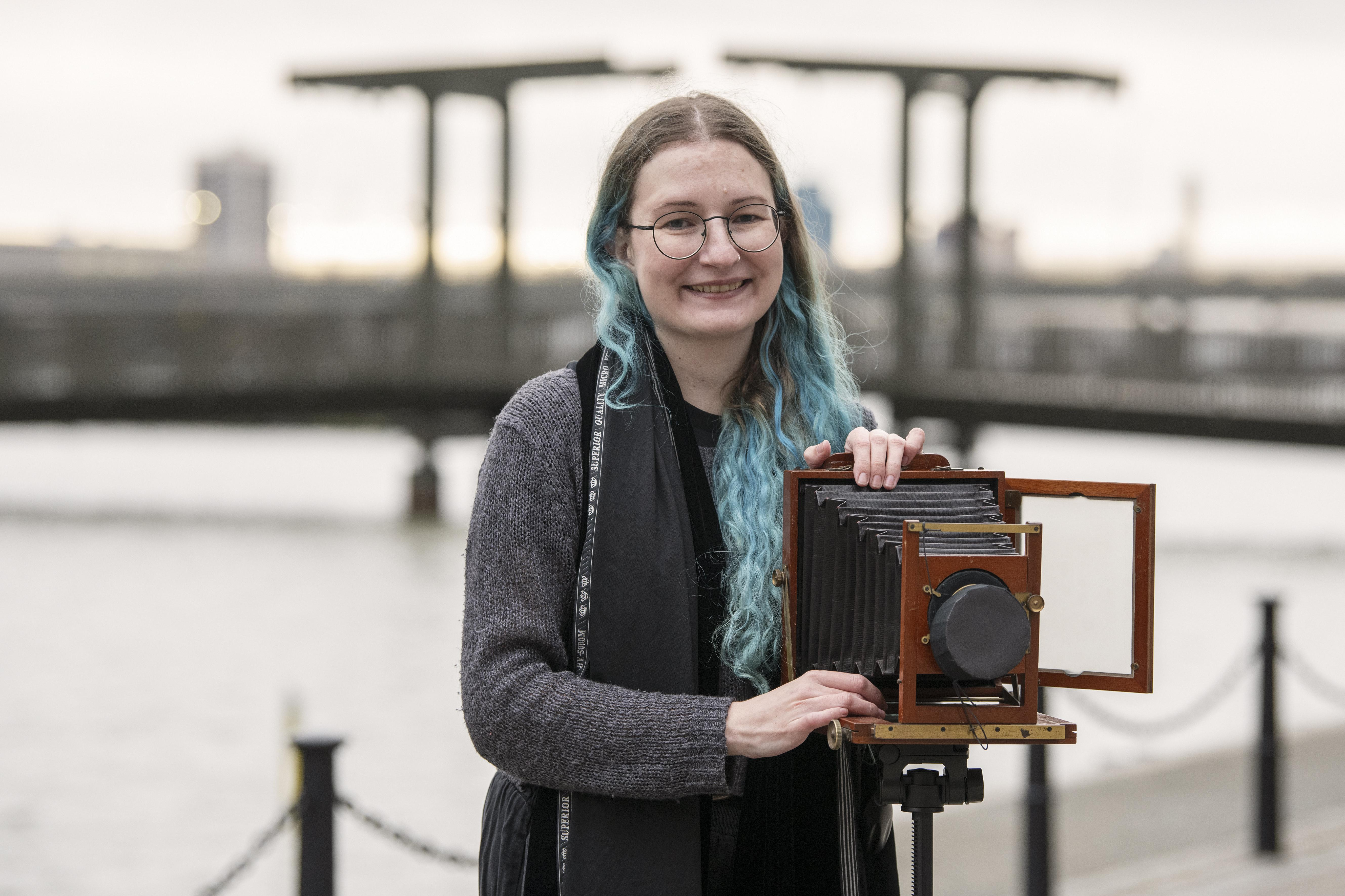 Woman by dock edge with antique camera