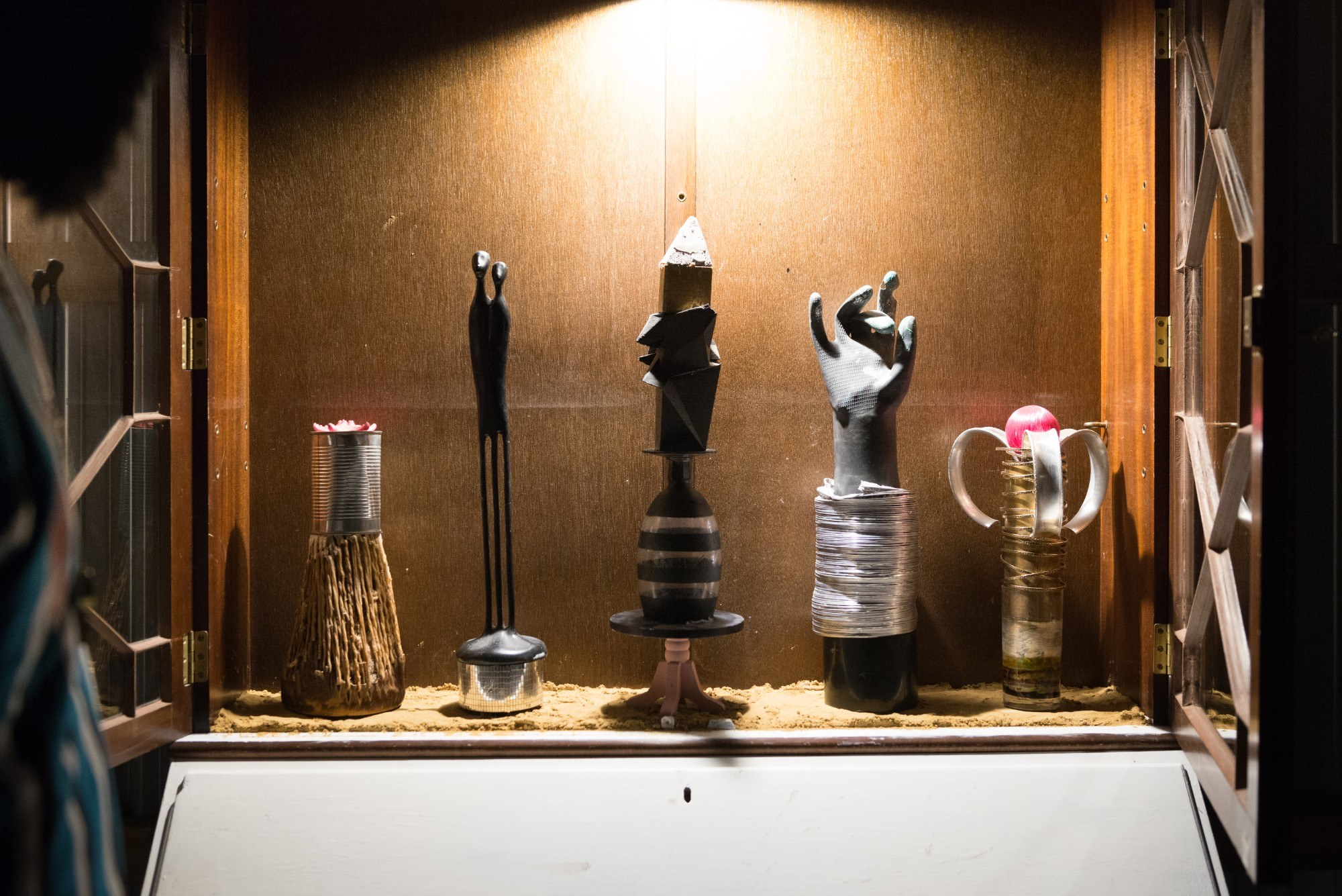 A trophy case with unusually shaped trophies inside, such as a hand and a tin can